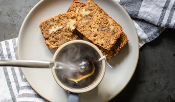 Sliced apple-walnut tea cake on a plate with a cup of tea.