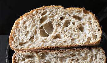 Naturally-leavened sourdough bread cut in half.