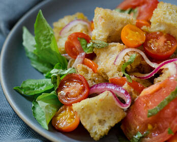 Three-tomato panzanella (bread) salad on a plate.